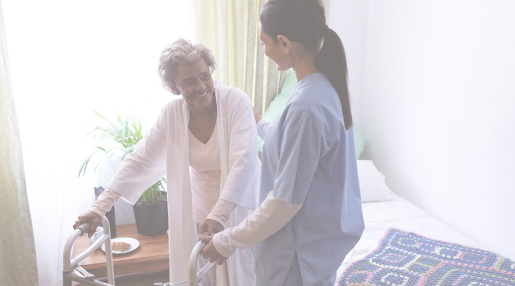 a nurse helping a senior patient using a walker out of bed
