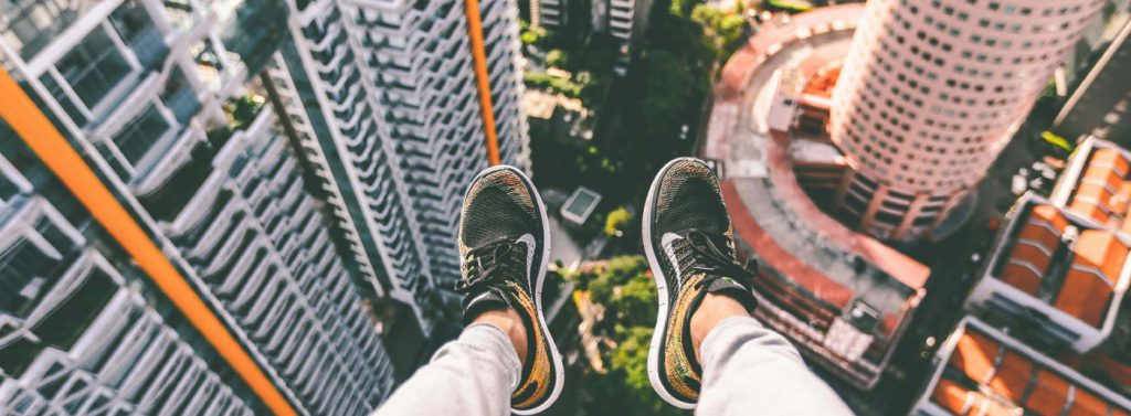 person sitting on a tall building with their feet hanging off the edge