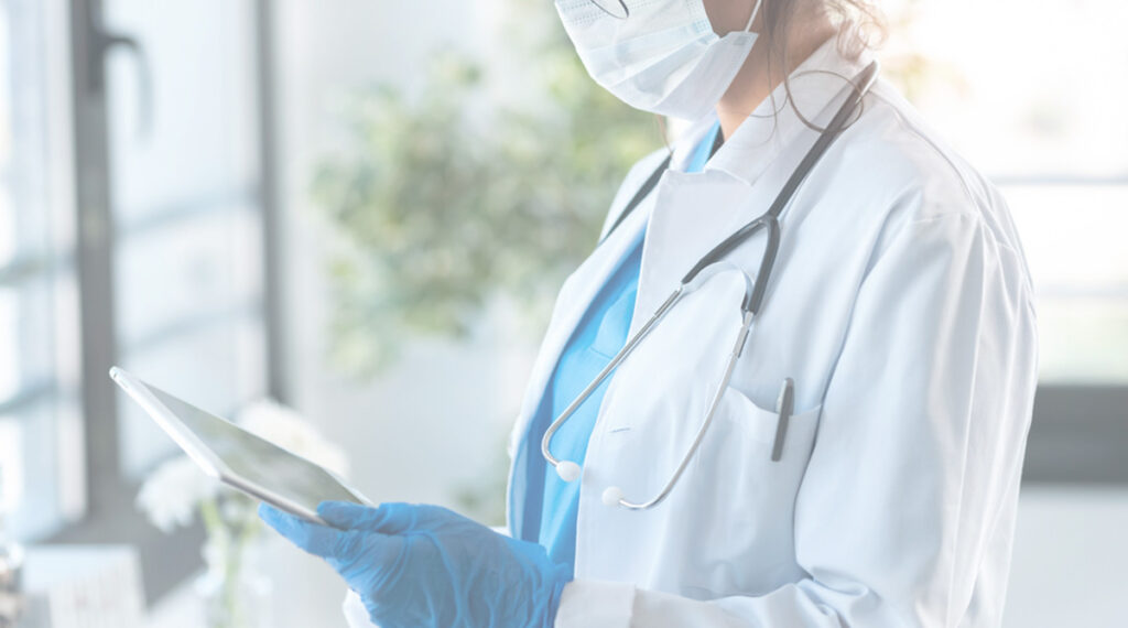 Doctor in ppe looking at ipad