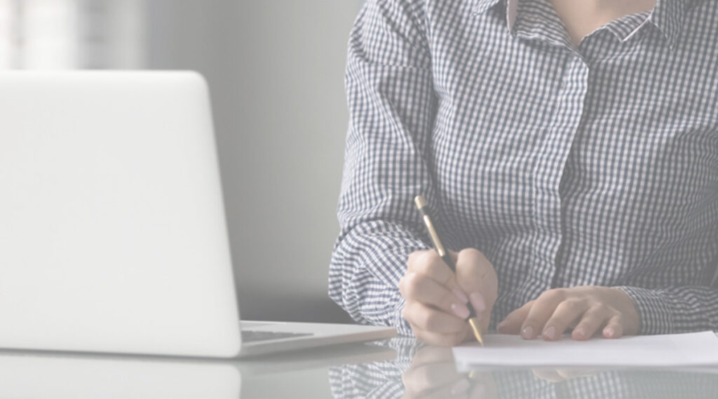 person writing in front of laptop