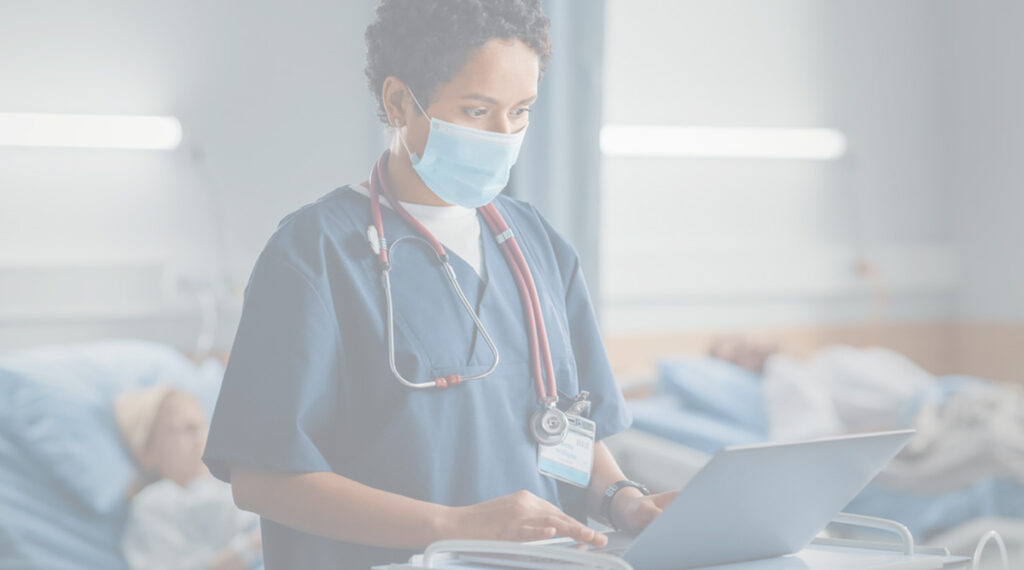 Professional Black Latin Female Head Nurse or Doctor Wearing Face Mask Uses Medical Computer. In the Background Patients in Beds Recovering Successfully after Sickness and Surgery